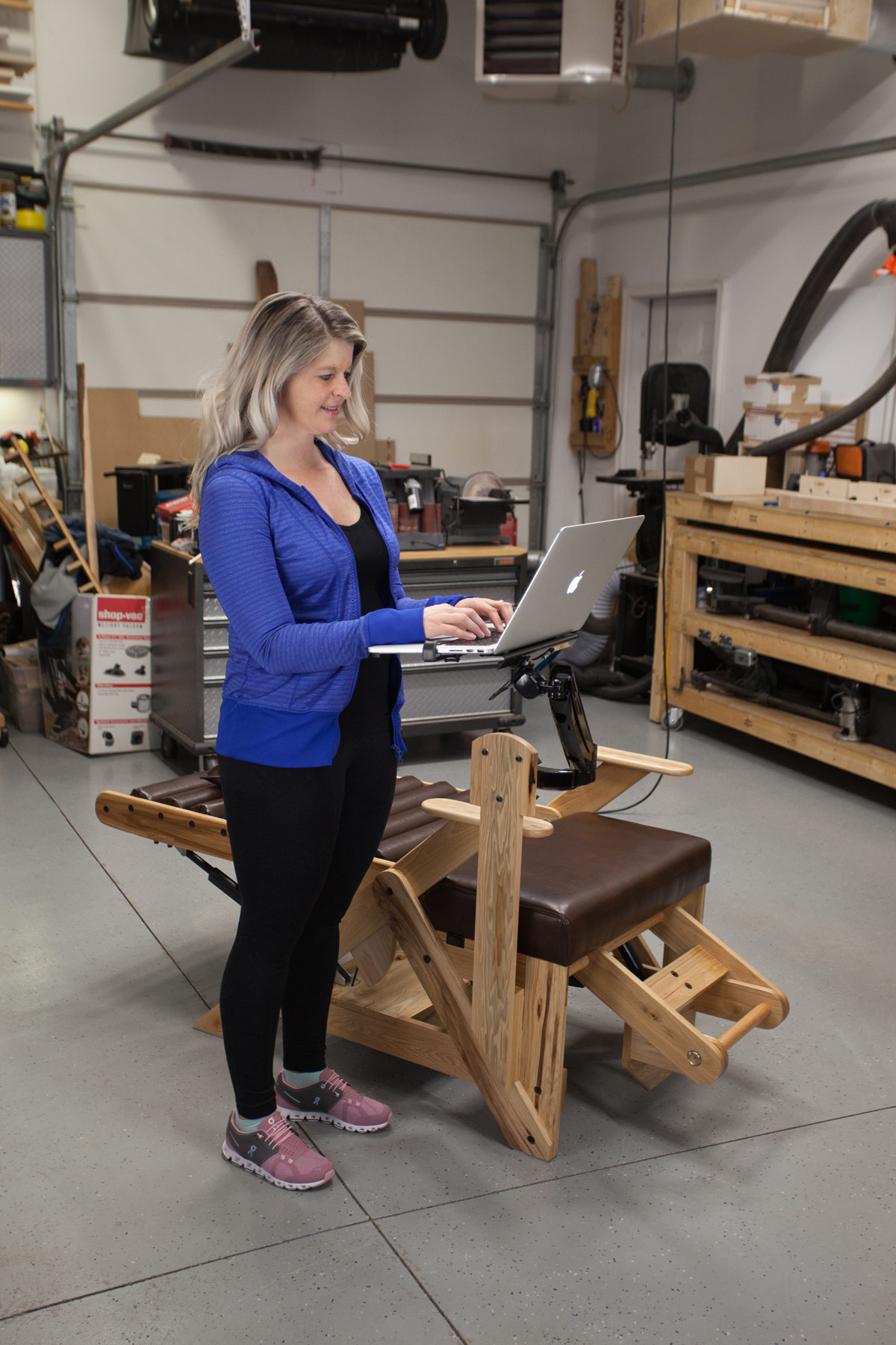 A woman standing and using a laptop computer with the inversion chair laptop arm attachment.
