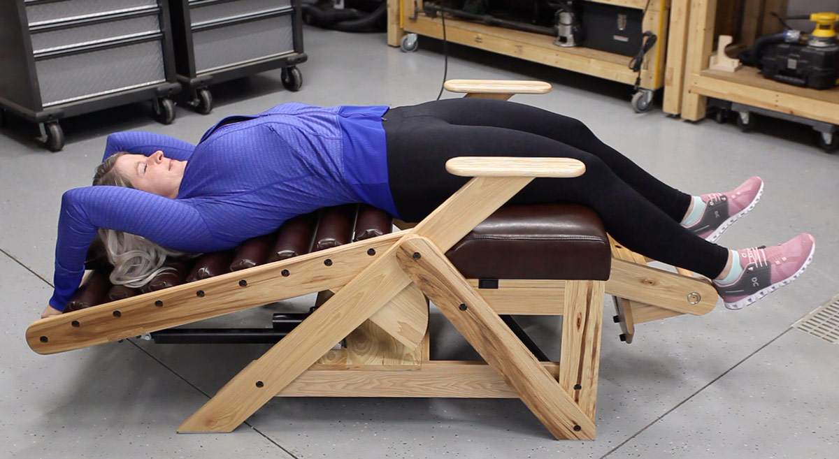 A woman using the pull bar on an inversion chair to add more spinal traction and to give a deeper stretch.