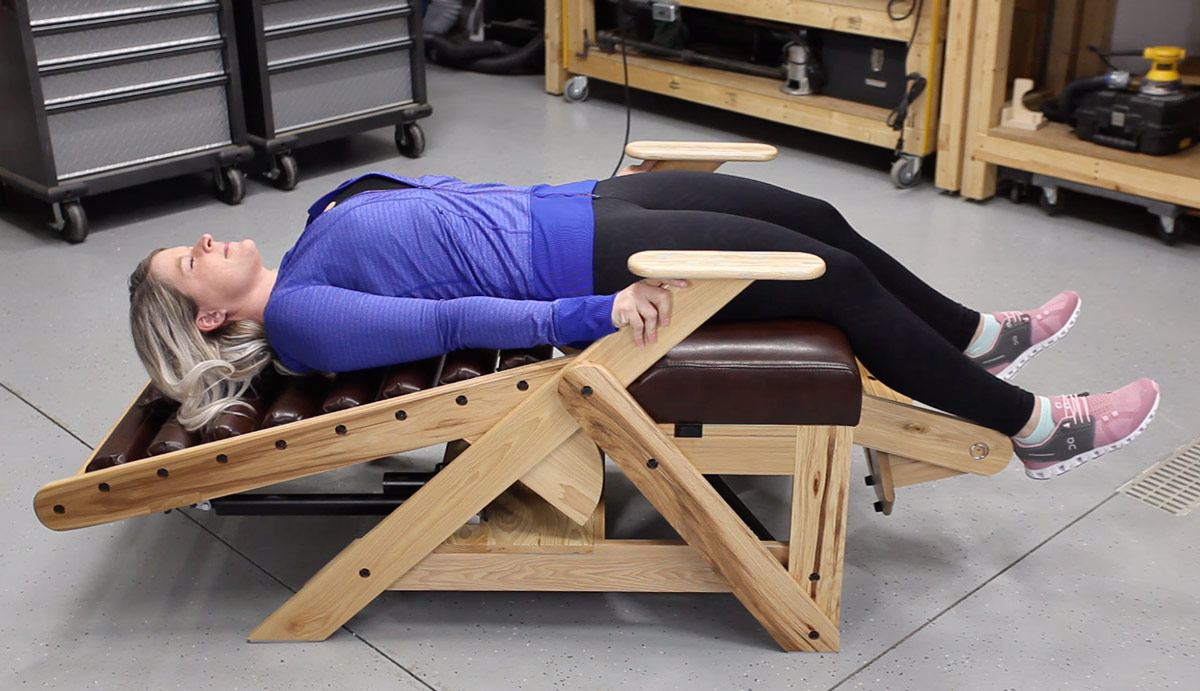 A woman using the traction handles on an inversion chair to add more spinal traction.