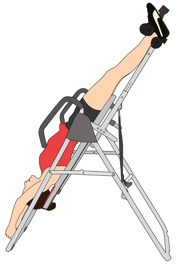 A woman using an inversion table with ankles strapped in and arms extended.